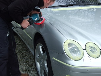 Polishing the car to a high gloss finish.